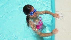 Маленькая девочка играя в бассейне сток-видео