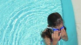 Маленькая девочка играя в бассейне видеоматериал