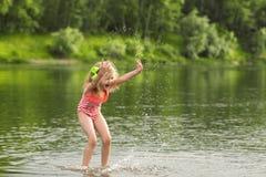 Маленькая девочка играя в воде и делая выплеск Стоковые Фото