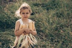 Маленькая девочка играя в кукурузном поле на осени Ребенок держа удар мозоли Сбор с детьми Деятельности при осени для детей стоковая фотография