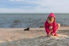 Маленькая девочка играя в песке на пляже моря, заходе солнца и меньших ветерке и, летние каникулы, развитии ребенка, improv здоро Стоковые Изображения