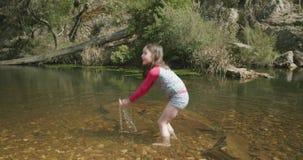 Маленькая девочка играя в щелчках реки мочит в свод и брызгает лодыжку глубоко акции видеоматериалы