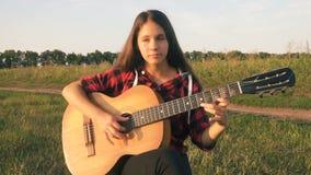 Маленькая девочка играя гитару на луге на заходе солнца сток-видео