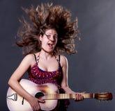 Маленькая девочка играя гитару стоковые изображения