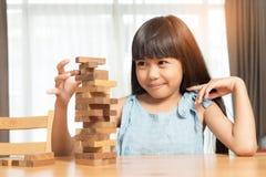 Маленькая девочка играя игру стога деревянных блоков стоковое фото rf