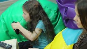 Маленькая девочка играя молодую женщину консоли, наркоманию игры, отдых видеоматериал