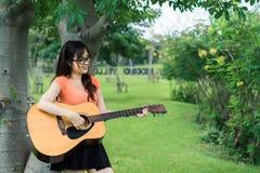 Маленькая девочка играя музыку с гитарой ослабляет стоковое фото rf