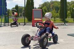 Маленькая девочка играя на спортивной площадке на теплый солнечный день стоковое фото rf