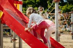 Маленькая девочка 2 играя на спортивной площадке Стоковые Изображения RF