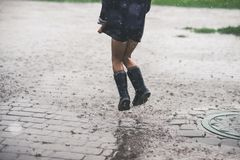 Маленькая девочка играя одно снаружи в плохой погоде стоковое фото rf