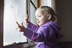 Маленькая девочка играя окном стоковая фотография