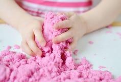 Маленькая девочка играя при розовое кинетическое образование песка дома предыдущее подготавливая для игры детей развития школы стоковые изображения rf