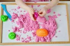 Маленькая девочка играя при розовое кинетическое образование песка дома предыдущее подготавливая для игры детей развития школы стоковые фотографии rf