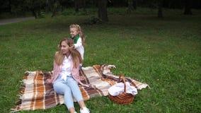 Маленькая девочка играя с ее мамой в парке осени 4K движение медленное акции видеоматериалы