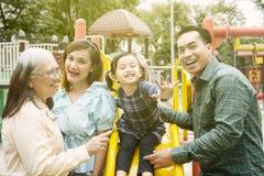 Маленькая девочка играя с ее семьей в спортивной площадке стоковая фотография