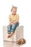 Маленькая девочка играя с зайчиком пасхи на белой предпосылке Стоковое Изображение RF