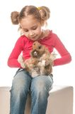 Маленькая девочка играя с зайчиком пасхи на белой предпосылке Стоковая Фотография