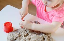 Маленькая девочка играя с кинетическим песком дома Стоковая Фотография RF