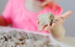Маленькая девочка играя с кинетическим песком дома Стоковое Изображение