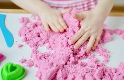 Маленькая девочка играя с кинетическим песком дома Стоковая Фотография