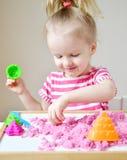Маленькая девочка играя с кинетическим песком дома Стоковое фото RF