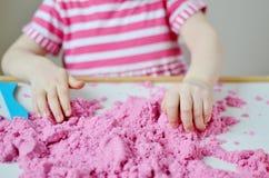Маленькая девочка играя с кинетическим песком дома Стоковые Изображения RF