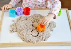 Маленькая девочка играя с кинетическим песком Стоковое Изображение
