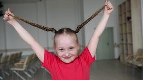 Маленькая девочка играя с отрезками провода Красивая девушка играет с ее волосами видеоматериал