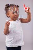 Маленькая девочка играя с пузырями мыла Стоковое Фото