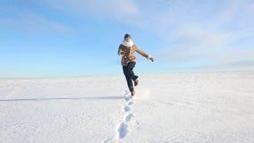 Маленькая девочка идет весело и скачет на покрытое снег поле Сцена потехи зимы солнечная с дорогой и снежным полем сток-видео