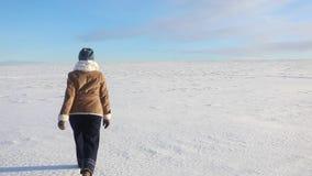 Маленькая девочка идет весело и скачет на покрытое снег поле Сцена потехи зимы солнечная с дорогой и снежным полем акции видеоматериалы