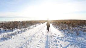 Маленькая девочка идет весело и скачет на покрытое снег поле Сцена потехи зимы солнечная с дорогой и снежным полем видеоматериал
