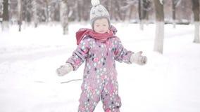 Маленькая девочка идет в снежный парк сток-видео