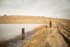 Маленькая девочка идет с собакой на береге озера стоковые фотографии rf
