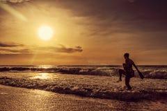 Маленькая девочка идя на пляж Cabo Ledo взаимодействуя с водой anisette вышесказанного стоковые изображения rf