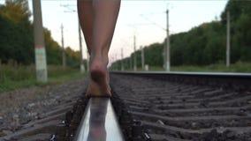 Маленькая девочка идя barefoot вдоль железнодорожного рельса видеоматериал