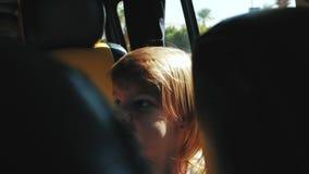 Маленькая девочка извивается в заднем сидении автомобиля видеоматериал