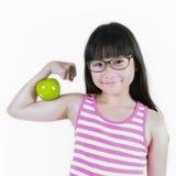 Маленькая девочка изгибает ее мышцу пока показывающ яблоко Стоковые Изображения RF