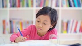 Маленькая девочка изучая на таблице в библиотеке видеоматериал