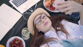 Маленькая девочка имбиря в стеклах лежа на одеяле в парке и делая selfie видеоматериал