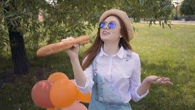 Маленькая девочка имбиря поя используя багет как микрофон в парке сток-видео