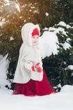 Маленькая девочка имея потеху в лесе зимы Стоковое Изображение