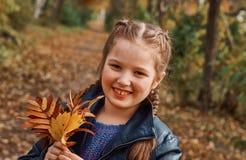 Маленькая девочка имея потеху на красивой осени Стоковое Изображение RF