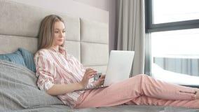 Маленькая девочка использует ноутбук рано утром в кровати акции видеоматериалы