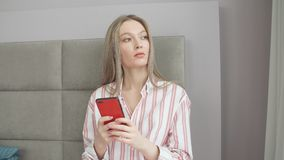 Маленькая девочка использует телефон в раннем утре в гостиничном номере видеоматериал