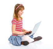 Маленькая девочка используя компьютер-книжку стоковое фото