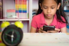 Маленькая девочка используя мобильный телефон дома стоковые изображения