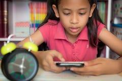 Маленькая девочка используя мобильный телефон дома стоковая фотография rf