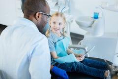 Маленькая девочка используя таблетку во время назначения с дантистом стоковые фотографии rf