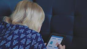 Маленькая девочка используя таблетку сидя на кресле дома ища что-то в онлайн магазине Ходящ по магазинам, социальные средства мас акции видеоматериалы